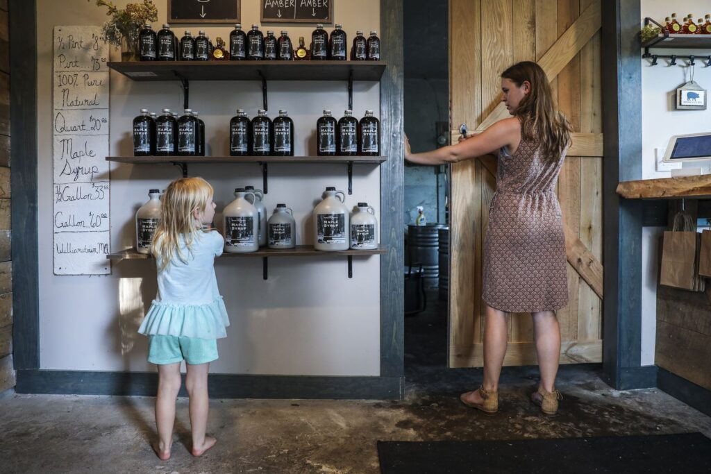 Nadia Lipinski, 5, moves around bottles of maple syrup in her family's store while spending time with her mom, Sarah Lipinski, owner of Sweet Brook Farm. ERIN CLARK/GLOBE STAFF
